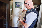 21 SEPTEMBER 2010 - PHOENIX, AZ: Phoenix detective Shane Forbes (CQ) examines a sawed off shotgun found in a home in central Phoenix. The shotgun's owner, allegedly a member of Hell's Angels, was arrested for owning a prohibited weapon because the shotgun's barrel was shorter than 18 inches. Crime has steadily dropped in Phoenix over the past few years, in line with national trends. The latest number released this month showed Phoenix reported fewer 2010 homicides, rapes, robberies, thefts - in addition to other major crimes -- compared with the same time period the previous year. Detectives in the Phoenix police department's Major Offender Unit make several arrests every day. PHOTO BY JACK KURTZ