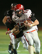 Iowa City High's Jake Leohr (18) is pulled down from behind by Linn-Mar's Austin Burbridge (15) during during the game between the Iowa City High Little Hawks and the Linn-Mar Lions at Linn-Mar Stadium in Marion on Friday October 12, 2012.