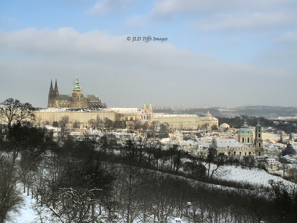 Hradcany and St. Vitus Cathedral seen from across the Strahov Monastery vinehards.  It is winter; ground, and roofs, are covered with snow.