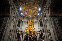 Altar of the Chair of St. Peter was designed by one of the great baroque artisans, Gianlorenzo Bernini who worked under the patronage of Pope Urban VIII and worked on the embellishment of the Basilica for 50 years.    Bernini created a large bronze throne in which it was housed, raised high on four looping supports held effortlessly by massive bronze statues of four Doctors of the Church, Saints Ambrose and Augustine representing the Latin Church and Athanasius and John Chrysostom, the Greek Church. The four figures are dynamic with sweeping robes and expressions of adoration and ecstasy. Behind and above the Cathedra, a blaze of light comes in through a window of yellow alabaster, illuminating, at its centre, the Dove of the Holy Spirit