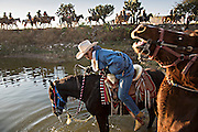 Mexican cowboys stop to water their horses during the annual Cabalgata de Cristo Rey pilgrimage January 5, 2017 in San José del Rodeo, Guanajuato, Mexico. Thousands of Mexican cowboys and horse take part in the three-day ride to the mountaintop shrine of Cristo Rey stopping along the way at shrines and churches.