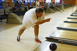 Visually-impaired man at ten pin bowling alley.