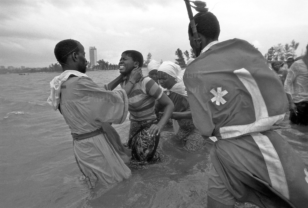 A priest of the Ebenezer Church performs some kind of exorcism on a teenage girl in the shallow waters of the Indian Ocean close to the capital.