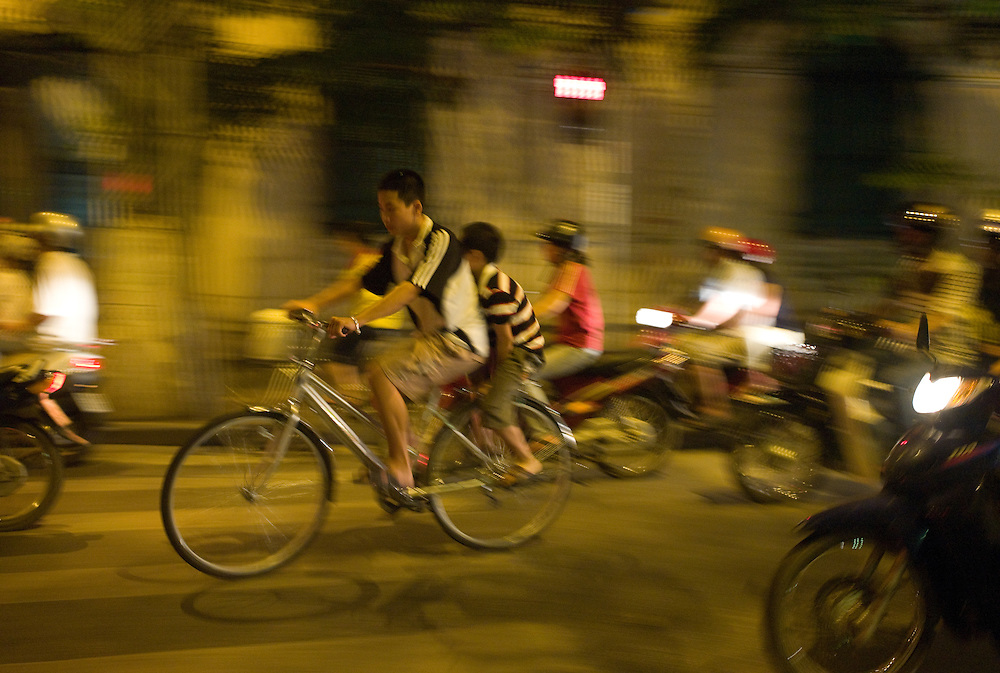 Two boys on a bike, amongst many motorcycles, Hanoi, Vietnam.