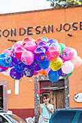A young girl sells balloons in the Plaza de la Soledad in the historic center of San Miguel de Allende, Mexico.