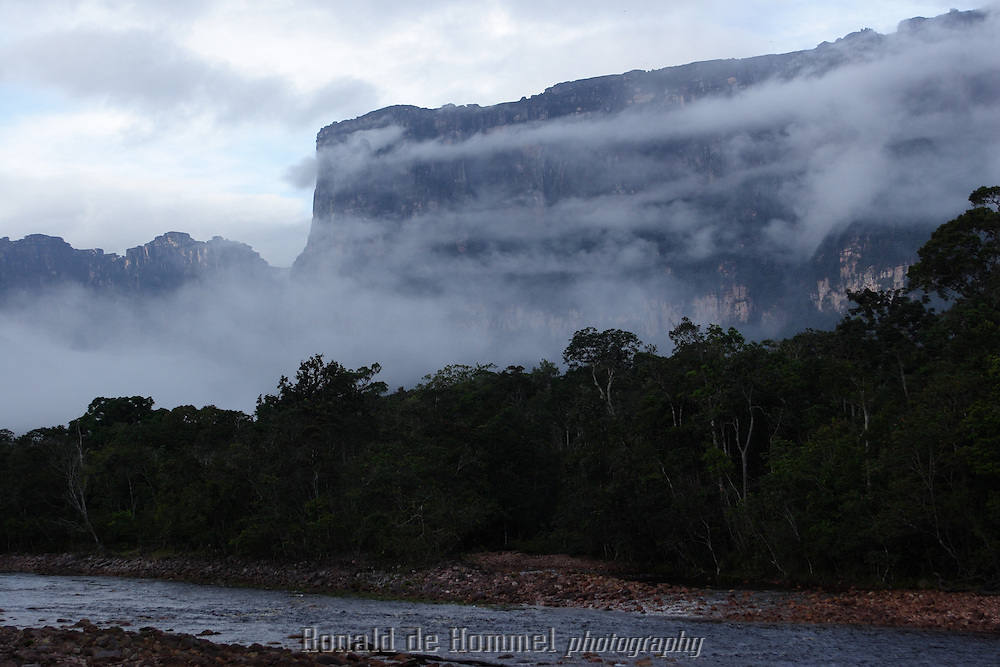 Canaima, Venezuela. National park Canaima in Central Venezuela is considered one of the most impressive natural sceneries in the world. On the edge of the Amazon basin this tropical forest area is a myriad of waterways separated by dense jungle and tabletop mountains called Tepuis with vertical cliffs of over 1000m. It's home to the highest waterfall in the world. The Angel Falls,are located in the centre of the park and have a continuous drop of 1000m. The remote area can only be reached by air or water, but the rivers are difficult to negotiate because of dangerous currents and rapids. From Canaima village canoe trips are organised to the Angel falls. The trip at high speed takes many hours and an overnight stay at the base of the falls is necessary.
