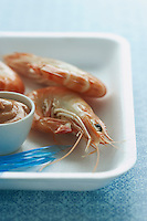 Shrimps and dipping sauce on plate close-up