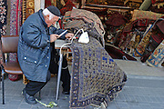 an old man fixing a carpet outside his shop in Jaffa, Israel