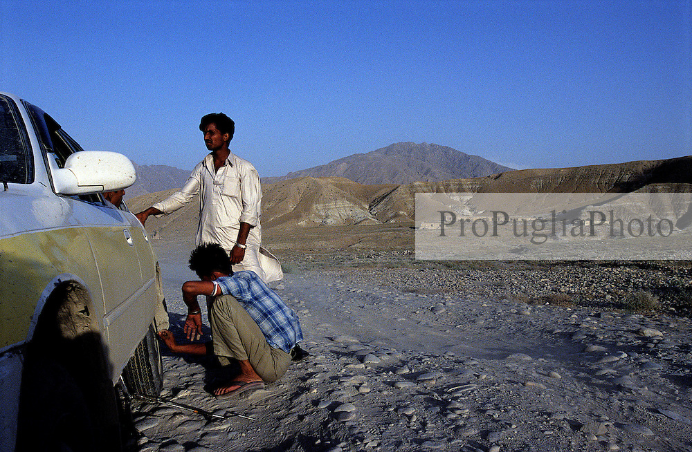 Somewhere in Nangarhar  one of the four passengers  of a 'Taxi to Kabul' replaces the back-left tyre of the vehicle..The Landscape is terrific.