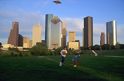 Stock photo of children flying a kite against a downtown skyline backdrop.