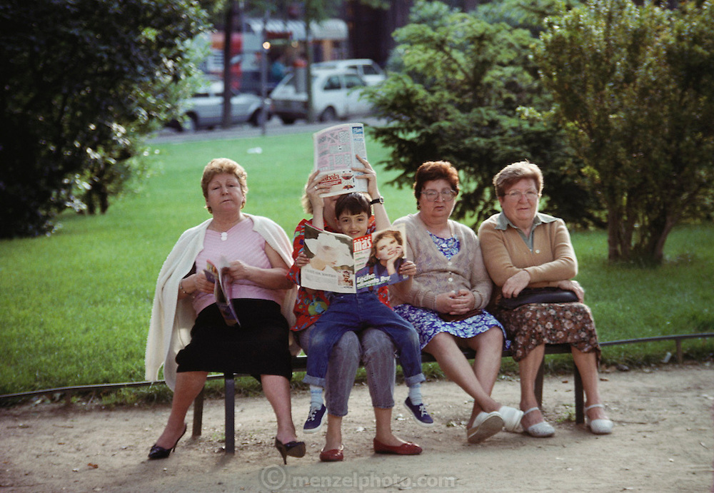 4 women and a boy reading magazine on a park bench by the Sagrada Familia, the  Gaudi Cathedral in  Barcelona, Spain.