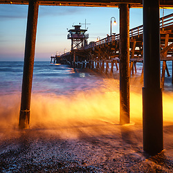 Under San Clemente pier at night during sunset photo. San Clemente California is a popular beach city in Orange County in the United States of America. Copyright ⓒ 2017 Paul Velgos with all rights reserved.
