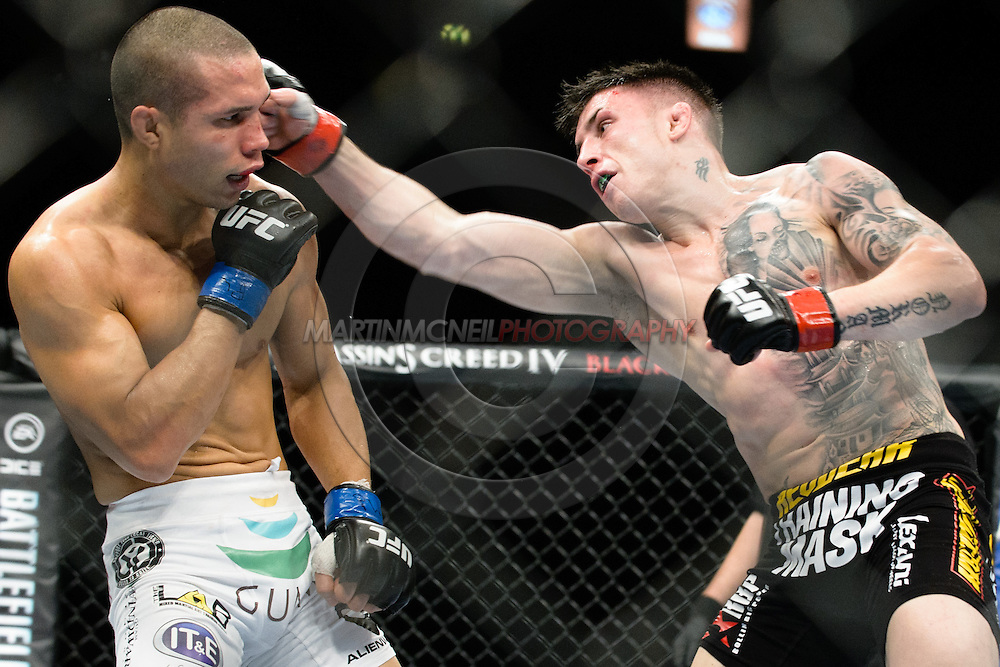 """MANCHESTER, ENGLAND, OCTOBER 26, 2013: Norman Parke (black shorts) and Jon Tuck (white trunks) compete during """"UFC Fight Night 30: Machida vs. Munoz"""" inside Phones4U Arena in Manchester, England (© Martin McNeil)"""