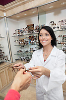 Happy eye specialist giving glasses to customer in store