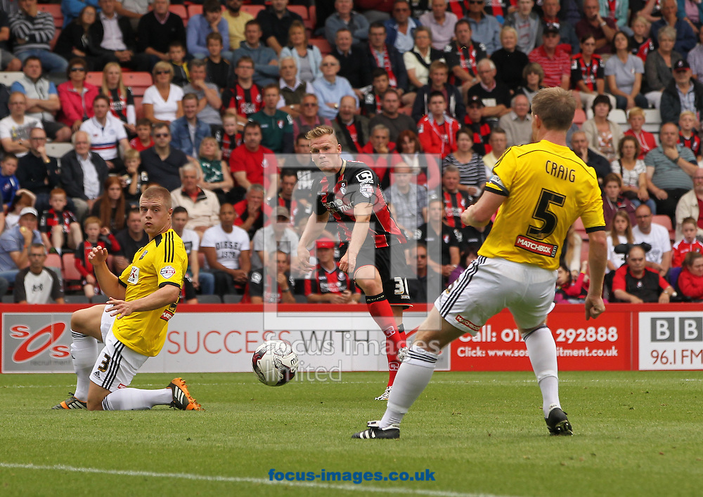 Matt Ritchie (centre) of Bournemouth takes a shot at goal during the Sky Bet Championship match at the Goldsands Stadium, Bournemouth<br /> Picture by Tom Smith/Focus Images Ltd 07545141164<br /> 16/08/2014