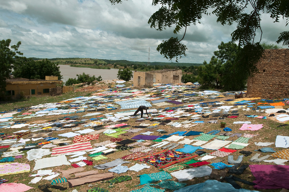 A man lays laundry out to dry in the sun in front of a colonial fort along the banks of the Senegal River. The Senegal River, which cuts through this part of the Western Sahel is central to daily life in the region. Men, often immigrants from neighboring Mali, make money washing clothes in the river for Senegalese families. <br /> Bakel, Senegal. 05/09/2010.