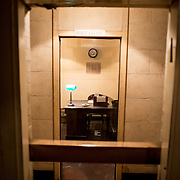 Looking through a doorway at Churchill's office at the Churchill War Rooms in London. The museum, one of five branches of the Imerial War Museums, preserves the World War II underground command bunker used by British Prime Minister Winston Churchill. Its cramped quarters were constructed from a converting a storage basement in the Treasury Building in Whitehall, London. Being underground, and under an unusually sturdy building, the Cabinet War Rooms were afforded some protection from the bombs falling above during the Blitz.