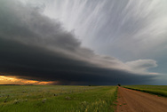 "After driving for over 5 hours I finally reached the edge of this powerful supercell just west of Faith, South Dakota. The shelf cloud looked amazing, backlit by the sunset and spitting out lots of lightning bolts. Once the storm hit it brought 1.5"" hail which left some dents in my car."