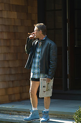Mature man standing on front porch holding a newspaper and smoking a cigar