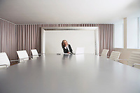 Female Business Executive Sitting in Boardroom using Laptop