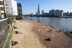© Licensed to London News Pictures. 25/02/2019. London, UK. People sunbathe on a beach on the banks of the River Thames in central London, on what is officially the hottest February day on record in Britain. Photo credit: Ben Cawthra/LNP