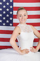 Portrait of young ballet dancer standing against American flag