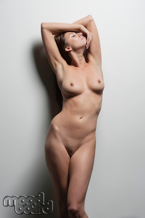 Sexy young naked woman posing over colored background