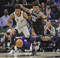December 23, 2017 - Sacramento, CA, USA - The San Antonio Spurs' Dejounte Murray (5) chases the ball after he blocked a shot by the Sacramento Kings' Kosta Koufos, not pictured, as the Kings' Frank Mason III (10) trails the play on Saturday, Dec. 23, 2017, at Golden 1 Center in Sacramento, Calif. (Credit Image: © Hector Amezcua/TNS via ZUMA Wire)