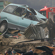 A damaged car amongst fallen debris in the City Centre after a Powerful earth quake ripped through Christchurch, New Zealand on Tuesday lunch time killing at least 65 people as it brought down buildings, buckled roads and damaged churches and the Cities Cathedral. Photo Tim Clayton