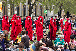 London, UK. 23rd April 2019. Climate change activists from Extinction Rebellion dressed in red to signify the blood of the dying planet cross Parliament Square during an assembly to discuss the preparation and delivery of activists' letters requesting meetings with Members of Parliament.