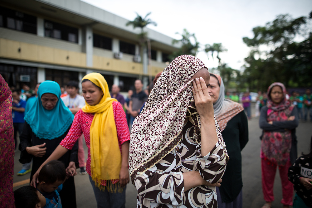 MARAWI, PHILIPPINES - JUNE 12: Muslim residents hides from the camera before a symbolic flag raising ceremony in celebration of the Independence Day in Marawi City, Philippines on June 12, 2017. As fighting rages on for the third week, police hung Philippine flags  around war torn Marawi to boost troop morale. (Photo: Richard Atrero de Guzman/NUR Photo)<br />  <br /> <br /> <br /> Residents in tears during Lanao Del Sur Vice Governor Mamintal Adiong's emotional address to the displaced families of Marawi. Local executives and citizens gathered for a symbolic flag raising ceremony to assert civilian authority and unity in celebration of Independence Day in Marawi City, Philippines on June 12, 2017. (Photo: Richard Atrero de Guzman/NUR Photo)