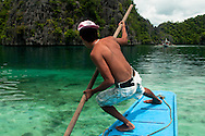 Philippines, Palawan. Boat driver on the way to a bay near Coron Island.