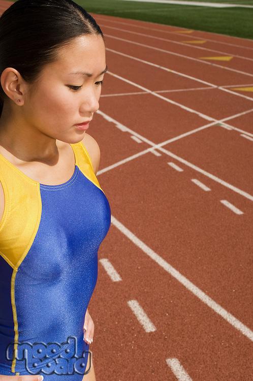 Female track athlete standing on track