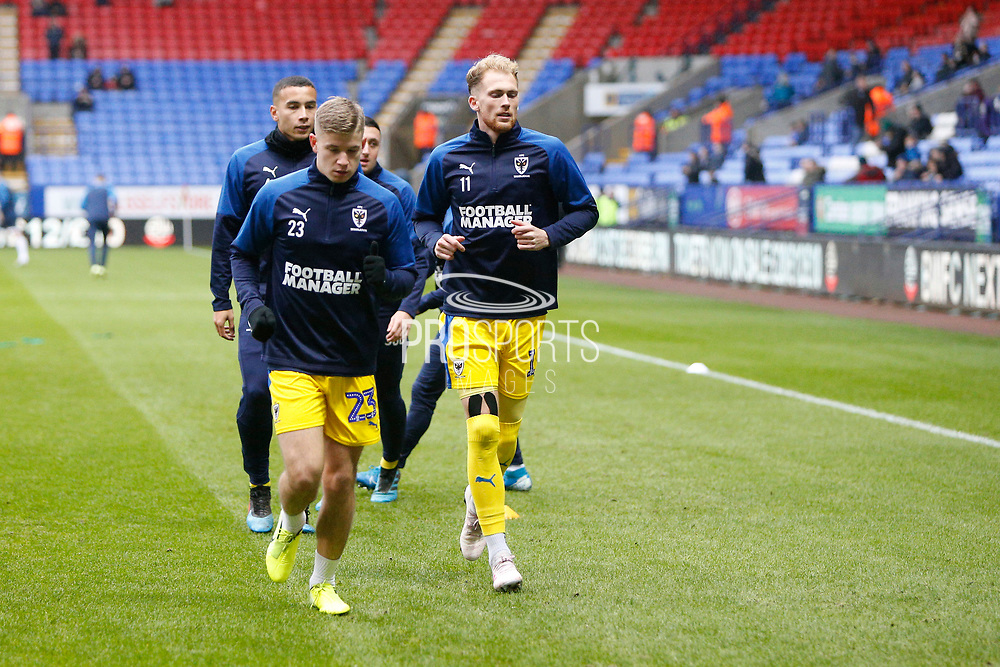 Max Sanders of Wimbledon and Mitch Pinnock of Wimbledon warming up during the EFL Sky Bet League 1 match between Bolton Wanderers and AFC Wimbledon at the University of  Bolton Stadium, Bolton, England on 7 December 2019.