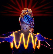 Portrait of a pretty blonde woman holding a giant glowing yellow spring.Black light