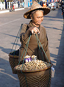 Myanmar woman carrying food to sell in baskets hanging on rod from shoulder; Tachilek; Myanmar