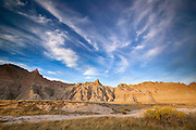 Several cirrus clouds hover over Saddle Pass in Badlands National Park, South Dakota.