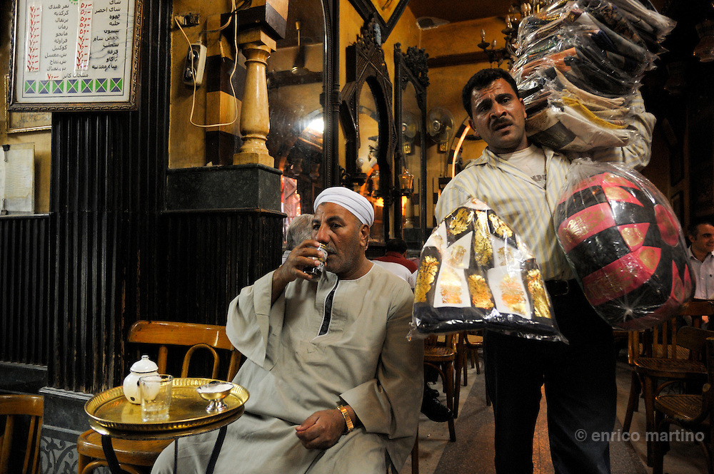 The famous tea and coffee house (ahwa) Al-Fischawi, in the hearth of one of largest Middle East bazaars, Khan el Khalili. Cairo's ahwa (the traditional coffeehouse) are for Cairo what the pub is to London or caffè to Rome. Once the ahwa was the main place for entairnement, a animated place where Cairo's men socialised playing chess, backgammon or domino, reading newspapers or watching TV, drinking Turkish coffee and shai (tea) with mint or smoking a sheesha, the tradional waterpipe. Some ahwa are meeting places for people loving chess or remembering famous Egyptian singer Oum Kalthoum. Today Cairo is changed and everybody is just too busy to drink coffee in a ahwa, so western style coffee shops are much more than traditional ahwa.