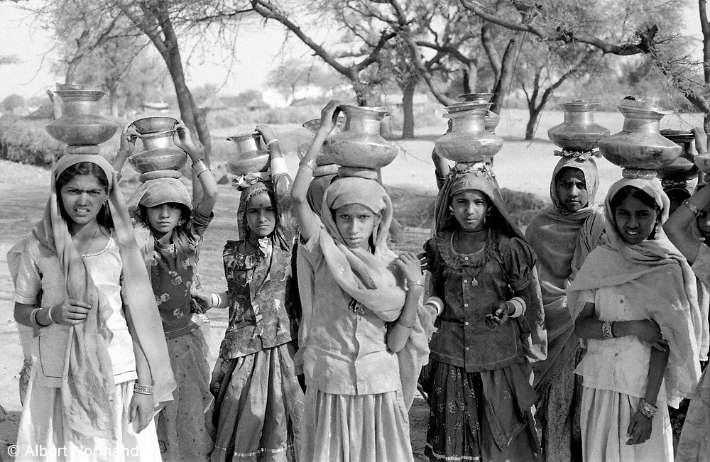 Young girls in traditional dress with water pots on head