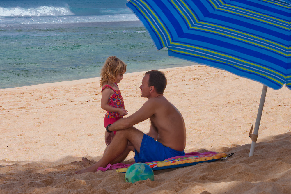 A father talks to his little girl on the beach in Hawaii