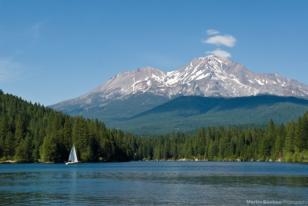 A lone sailboat drifts on Lake Siskiyou below Mount Shasta, summer, Shasta-Trinity National Forest, California