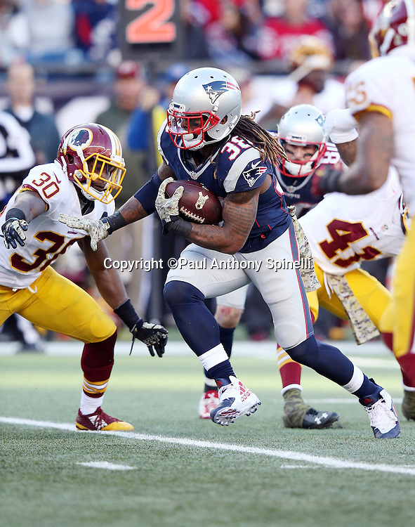 New England Patriots running back Brandon Bolden (38) tries to avoid tackle attempts by Washington Redskins strong safety Kyshoen Jarrett (30) and Washington Redskins inside linebacker Perry Riley, Jr. (56) as he runs the ball in the fourth quarter during the 2015 week 9 regular season NFL football game against the Washington Redskins on Sunday, Nov. 8, 2015 in Foxborough, Mass. The Patriots won the game 27-10. (©Paul Anthony Spinelli)