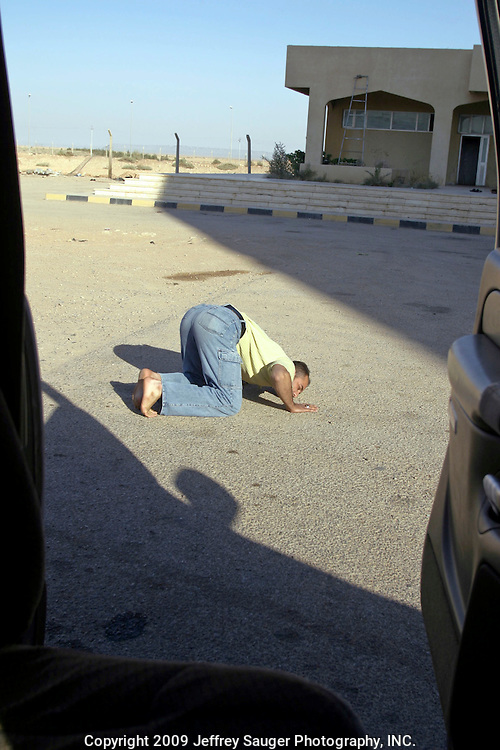 Emad Al-Kasid, kisses the ground in Al Quim, Iraq, as the Al-kasid family finally clears the Syrian-Iraqi border at about 8:30a.m. Sunday, July 20, 2003. The family is returning back to its home city of Nassiriyah, Iraq, for the first time since 1991 after fighting in the failed uprising against Saddam Hussein, fleeing to a refuge camp in Saudi Arabia for 3 years and finally settling in Dearborn, MI.Emad Al-kasid has been planning the trip home for the past year. He's met with U.S. government officials from Paul Wolfowitz to Joseph Biden trying to get permission for a delegation to return to help rebuild his country. He finally decided to make the trip with his family and a few others.