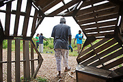"""mkb081217/metro/Marla Brose --   A man leaves the shade of  """"The Hive"""" a sculpture made out of wood crates, to resume work cultivating vegatables at Tres Hermanas Farm. (Marla Brose/Albuquerque Journal)"""