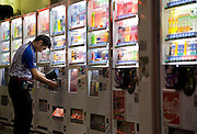 An owner checks vending machines in Tokyo, Japan on 29 April 2010. Photographer: Robert Gilhooly