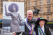 Peter Barratt carries a picture of his Great Grand mothe, sufragette Alice Hawkins - #March4Women 2018, a march and rally in London to celebrate International Women's Day and 100 years since the first women in the UK gained the right to vote.  Organised by Care International the march stated at Old Palace Yard and ended in a rally in Trafalgar Square.