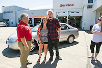 Paul Gaudet Jr. with Joanna Griffiths as she receives a thankful hug from Kyle Bigler standing in front of Bigler's new 2005 Honda Accord on Tuesday morning at AutoServe of Tilton.  (Karen Bobotas/for the Laconia Daily Sun)