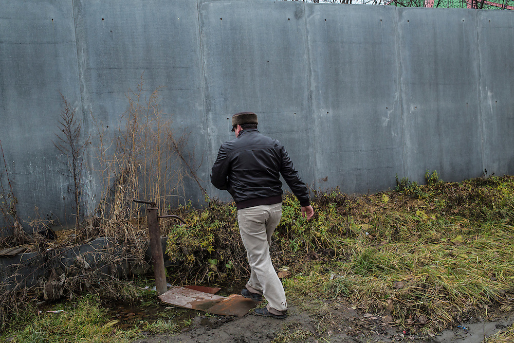Local journalist Yuri Druzhinin walks to a water pump to wash mud from his hands on Monday, November 11, 2013 in Asbest, Russia.