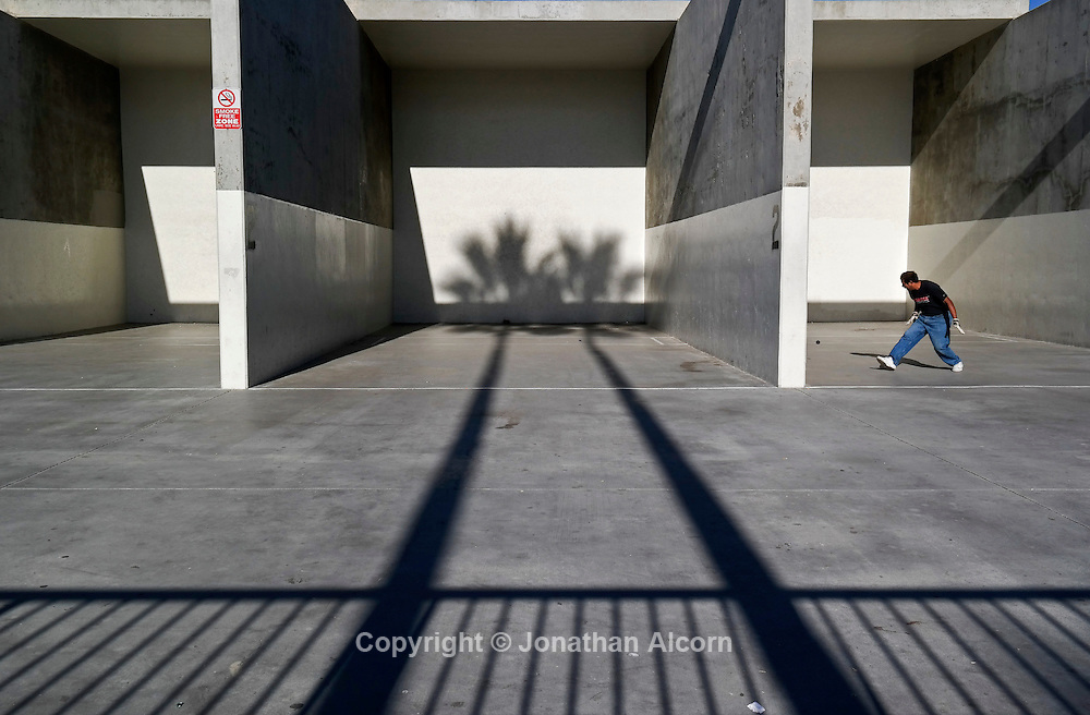 Palm trees cast shadows as a lone man practices at the Venice Beach recreation center handball courts.