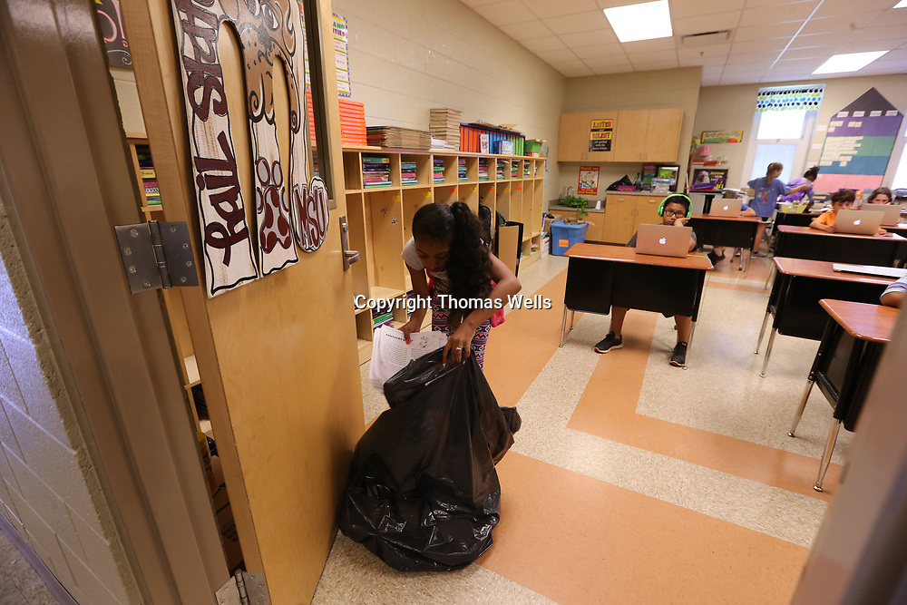 Totianna Damron 10, helps throw away papers and other items as she helps clean the classroom during her last day of school at Corinth Elementary School on Thursday.